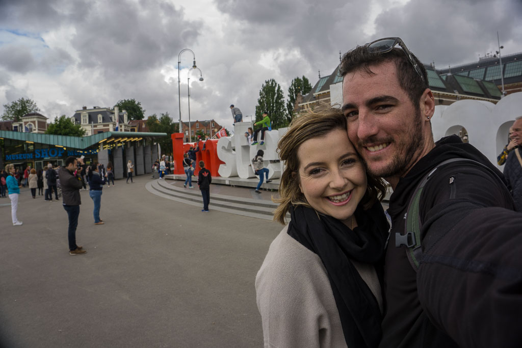 The Two Drifters being tourists in front of the I Amsterdam sign - The Two Drifters www.thetwodrifters.net